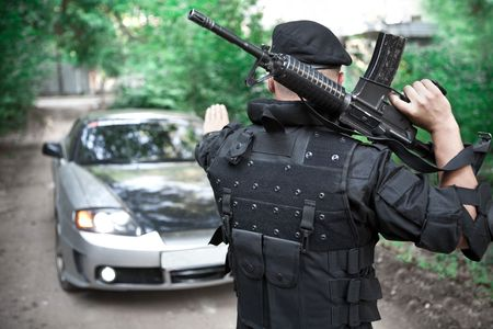 roadblock: Warrior with the M4 rifle is stopping the car on the roadblock Stock Photo