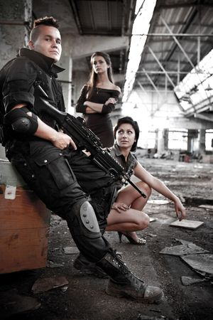 Armed mercenariy with machineguns and 2 pretty girls on the ruined building background. photo