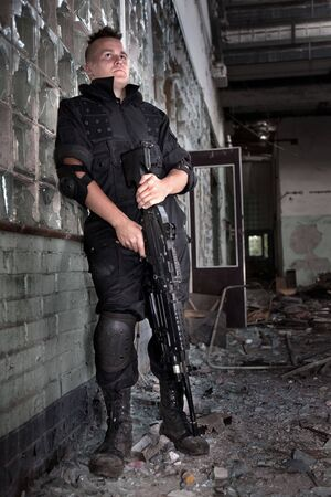 Warrior with the machine gun on the ruined building background. photo