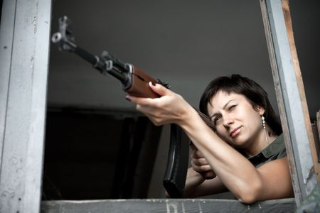 windows frame: Aiming woman with machine gun.