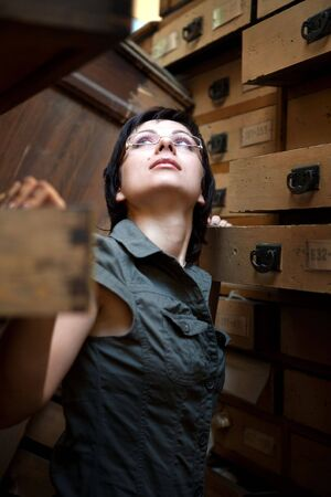 Sexy girl is trying to find something in the old archive. Stock Photo - 5282787