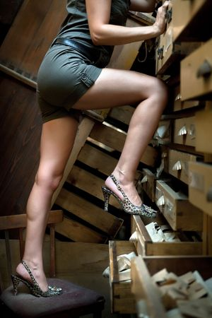 legs open: Sexy girl is trying to climb the secretary using shelves as a stairs.