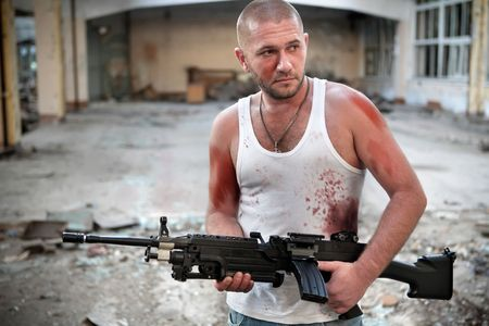 hoodlum: Armed rebel in bloody t-shirt with machinegun on the ruined building background.