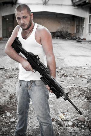 machine-gun: Gewapende rebellen in t-shirt met het machinegeweer op de verwoeste gebouw achtergrond. Stockfoto