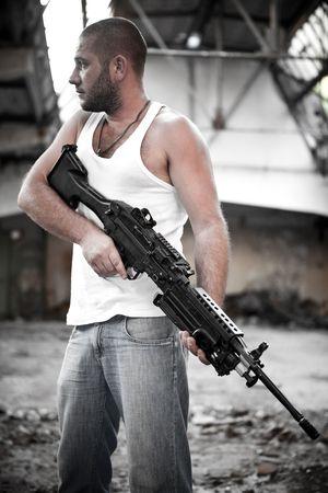 machine-gun: Gewapende rebellen in t-shirt met het machinegeweer op de achtergrond geruïneerd gebouw. Stockfoto