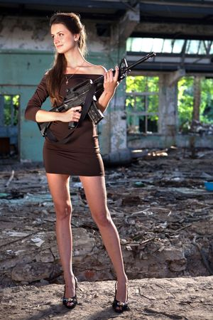 holding head: Portrait of a woman with the M4 machine gun. Stock Photo
