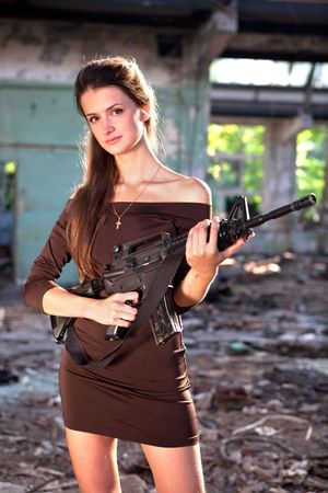 holding gun to head: Portrait of a woman with the M4 machine gun. Stock Photo