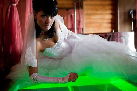 Pretty bride with bouquet is laying on the glass floor lighted with green. Focus point on the face. photo