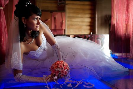 Pretty bride with bouquet is laying on the glass floor lighted with blue. Focus point on the face.  photo