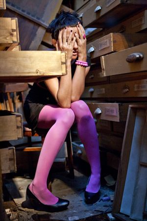 Pretty woman in grief  in the ruined office among opened cabinet drawers. Stock Photo - 5620654