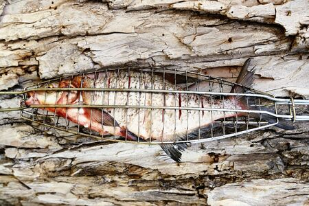 Grilled fish on the wooden cork background. photo