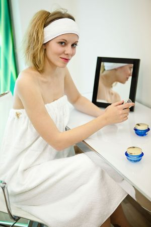 Pretty girl in the towel is going to make a make-up near the mirror photo