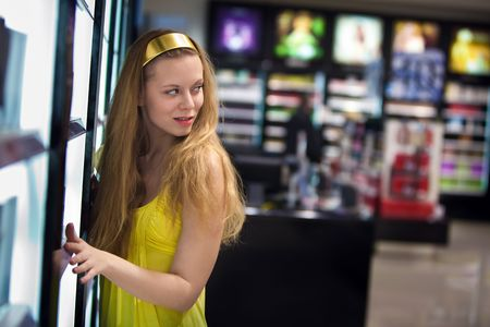 Pretty blond girl in the shop. Blurred colorful stillages on the background. photo