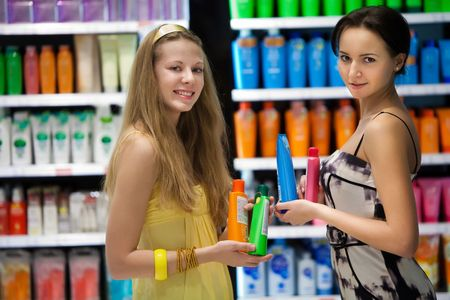 Pretty girls in the shop with a cosmetics. Blurred colorful showcases on the background.