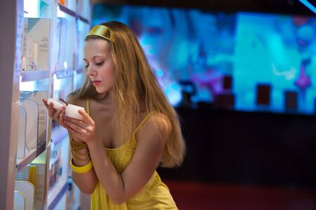 Pretty blond girl in the shop. Blurred colorful background. photo