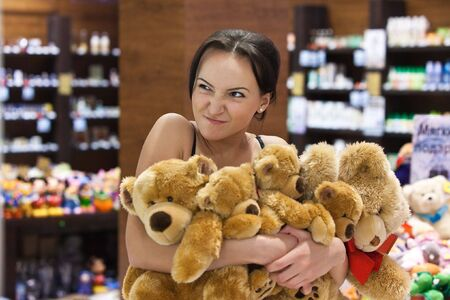 Greedy girl in the shop is embracing a heap of teddy bears. Blurred colorful background. photo