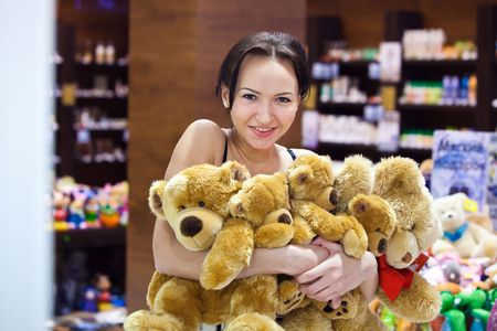 Pretty girl in the shop is embracing a heap of teddy bears. Blurred colorful background. Stock Photo - 5941668