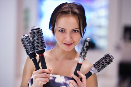Pretty girl with the hair brushes. Blurred colorful background. photo