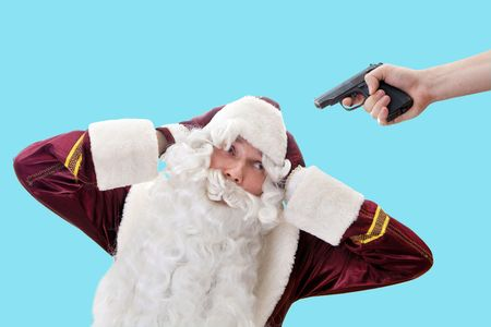 pitiful: Pitiful Santa under the pistol hindsight. Isolated on blue.