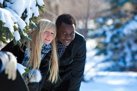 Blond girl and dark-skinned boy in the winter forest.  photo