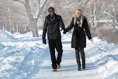 Romantic multi-etnic couple is walking in the winter park photo