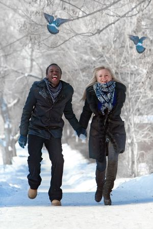 Romantic multi-etnic couple is running in the winter park frightening pigeons Stock Photo - 6320268