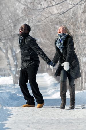 Laughing multi-etnic couple in the winter park photo
