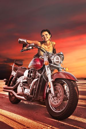 Sexy girl on the big chromed motorcycle on the sunset background.