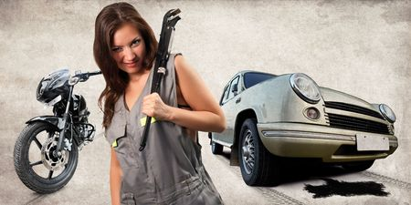 Pretty mechanic with the adjustable wrench. Broken car and bike on the background.