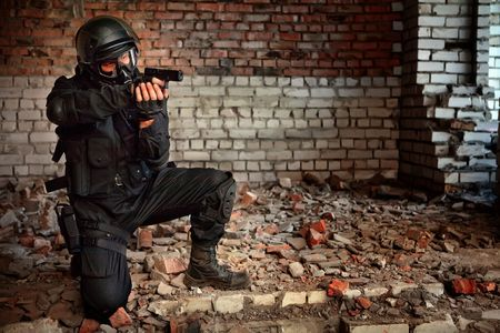work force: Armed man in protective cask with a pistol on the ruined building background. Stock Photo