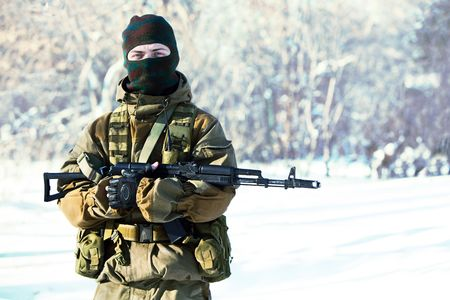 sniper training: Russian soldier in winter uniform with the machine gun on the forest background.