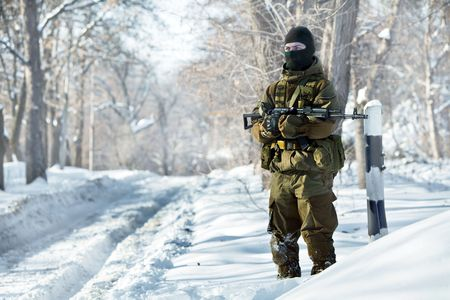 russian hat: Russian soldier in winter uniform with the machine gun on the forest background.