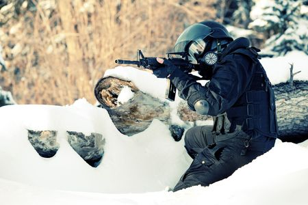 NATO soldier in winter uniform with the M4 machine gun on the forest background.