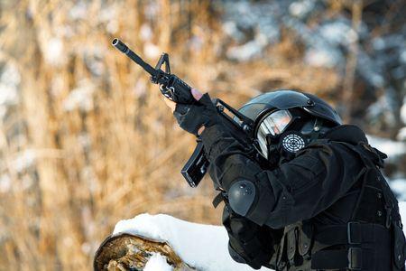 Soldat de l'OTAN en uniforme d'hiver avec la mitrailleuse M4 sur le fond de la forêt.