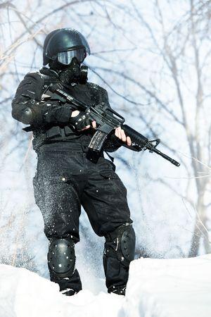 soldier in winter uniform with the M4 machine gun on the forest background. Standard-Bild