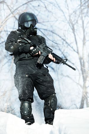 soldier in winter uniform with the M4 machine gun on the forest background. Stock Photo