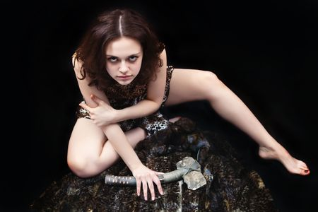 Prehistoric woman with the stone axe is sitting on the fur underlay near the fire. photo