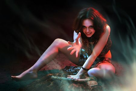 Prehistoric woman with the stone axe is sitting on the fur underlay near the fire.  Stock Photo - 6534264
