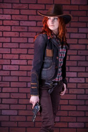 Pretty redhaired cowgirl with the revolver. Brick background. photo