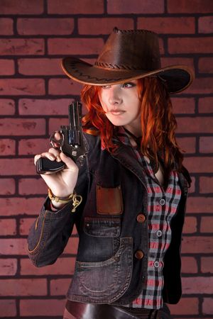Pretty cowgirl with the revolver. Brick background.