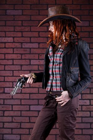 Pretty redhaired cowgirl is checking the bullets in the gun. Brick background. photo
