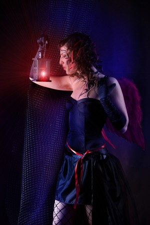Beautiful dark angel is blowing out the red lantern.  photo