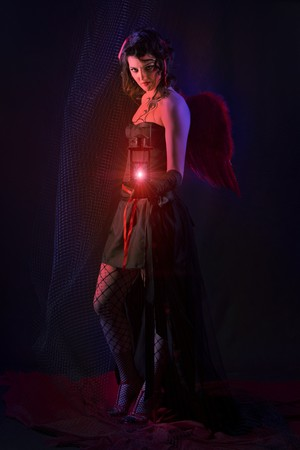 Beautiful dark angel is holding an old lantern. Stock Photo - 6941800