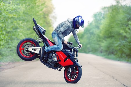 Stunt rider making stoppie on the summer forest background