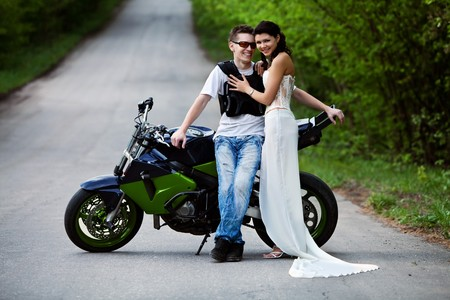 Beautiful smiling couple near powerfull sport motorbike. Forest road on the background. photo