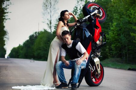 Pretty couple near breakdowned motorbike on the center of the rural road. photo