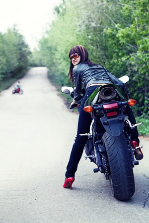 Pretty girl in the leather jacket is looking back sitting on the modern sport motorbike. Another biker on the background.