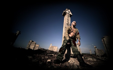 possessed: Bloody zombie in the military uniform under the radiation sign on the ruined buildings background.
