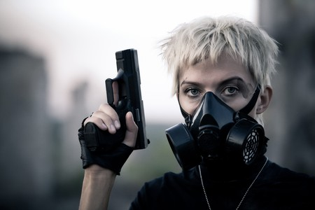 face guard: Blond woman in the gas mask with the pistol  Stock Photo