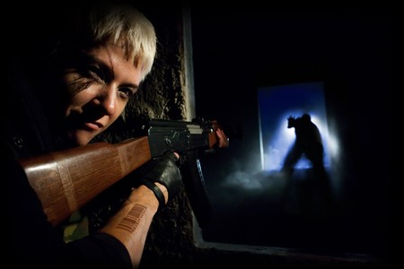 Blond woman with machine gun is aiming on silhouette. photo